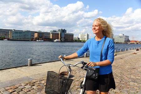 scandinavian people: Danish woman walking in Copenhagen harbour with bicycle.