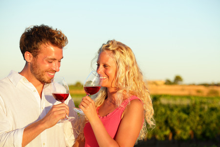 Happy people drinking rose wine alcohol laughing in summer vineyard. photo
