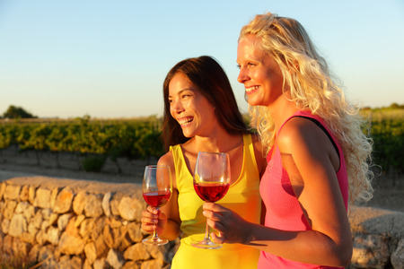 Happy women holding glasses of red wine or rose enjoying a glass outside at sunset. photo