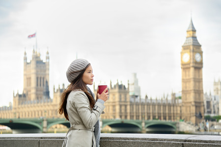 winter palace: London woman drinking coffee by Westminster Bridge.