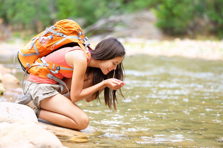 Hiker woman drinking water from river creek hiking in Zion National Park.  Stock Photo