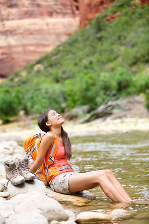 Relaxing hiker woman resting feet in river happy serene and relaxed after hiking in Zion National Park. photo