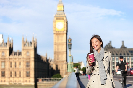 London woman happy by Big Ben laughing and drinking coffee in autumn.  photo