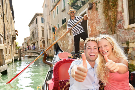 Travel concept - happy couple Venice gondola giving thumbs up hand sign excited looking at camera. photo