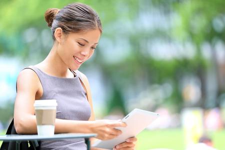 persona leyendo: Mujer de negocios que usa la tableta en la hora del almuerzo en el parque de la ciudad. Foto de archivo