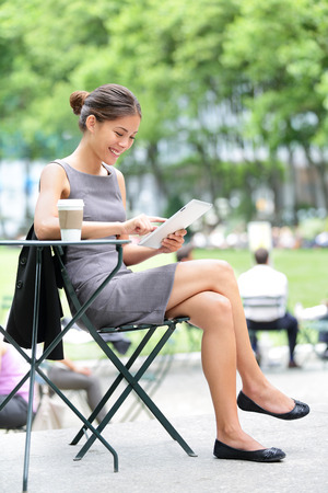 bryant: Young professional business woman using tablet computer in Bryant Park, New York City, USA.  Stock Photo