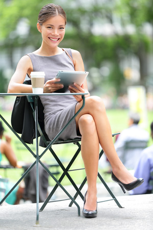 bryant park: Business woman using tablet on coffee break in city park.