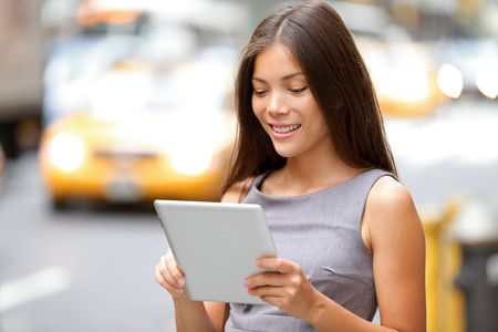 Tablet computer businesswoman in New York City, standing outside in street.  photo