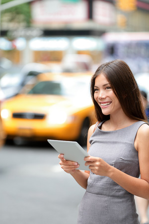 Tablet computer business woman in New York City, standing in street with yellow taxi cab.  photo