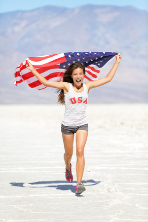 Athlete woman with american flag running with USA t-shirt showing winning gesture excited and happy outdoor in desert nature. Cheerful fitness woman winner cheering.