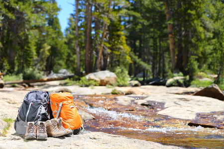 Hiking backpacks and hiker shoes. Hike concept of trekking hike gear equipment from couple on travel trip.