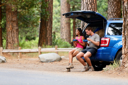 yosemite: Couple on car road trip travel in eating in forest having lunch break outdoors smiling happy. Multiracial couple, Asian woman, Caucasian man People in Yosemite National Park, California, United States