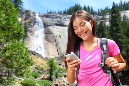 active: Smartphone - woman hiker using smart phone app on travel hike living healthy active lifestyle by waterfall in Yosemite National Park, California, USA.