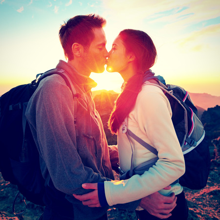 Kiss - couple kissing romantic at hiking sunset sharing embrace enjoying sunshine and love on beautiful hike in mountain nature landscape. Young interracial couple, Asian woman, Caucasian man in love. photo