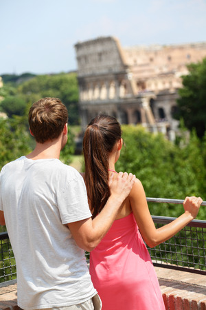 tourist tourists: Romantic couple tourists by Colosseum, Rome, Italy. Happy lovers on honeymoon travel in front of Coliseum. Love and travel concept.