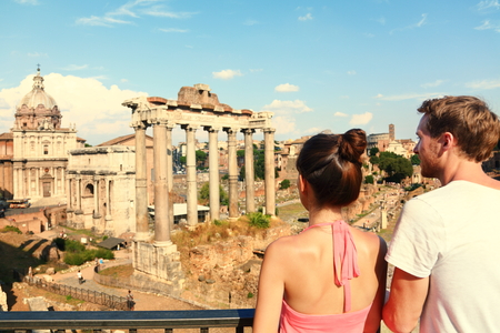 Rome tourists looking at Roman Forum landmark in Rome. Couple sightseeing on travel vacation in Rome, Italy. Happy tourist couple, man and woman traveling on holidays in Europe.