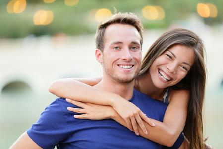 Jong koppel. Happy jonge college universitaire studenten lachend in de camera portret. Multiraciale vrouw en man in de liefde.