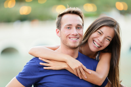 Young couple. Happy young college university students smiling at camera portrait. Multiracial woman and man in love.