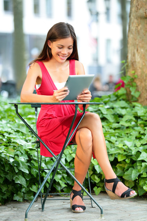bryant park: Young asian woman using tablet pc in Bryant Park, Manhattan, New York City. Young casual woman using tablet computer app and 4g network Stock Photo
