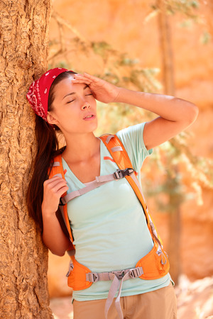 Dehydration thirst heat stroke exhaustion concept with woman hiker tired, dehydrated and exhausted Bryce Canyon. Girl tired close to heat stroke due to high temperature and lack of water. photo