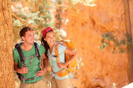 Hiking - young couple of hikers relaxing resting in Bryce Canyon walking smiling happy together. Multiracial couple, young Asian woman and Caucasian man in Bryce Canyon National Park landscape, Utah photo