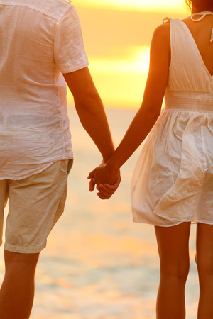 Romantic couple holding hands on beach sunset during travel. Happy woman and man in romance on honeymoon romance in beautiful sun light. photo