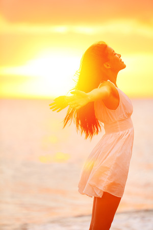 arms raised: Freedom woman enjoying feeling happy free at beach at sunset. Beautiful serene relaxing woman in pure happiness and elated enjoyment with arms raised outstretched up. Asian Caucasian female model.