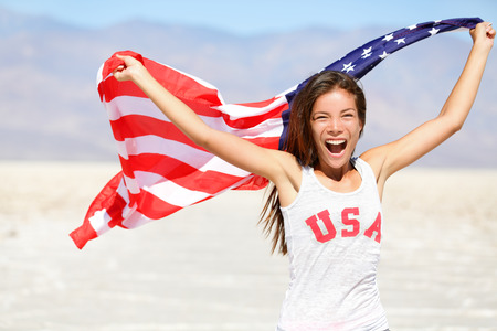 American flag - woman USA sport athlete winner cheering waving US flag Stars and Stripes outdoor running in nature. Beautiful cheering happy young multicultural girl joyful and excited. photo