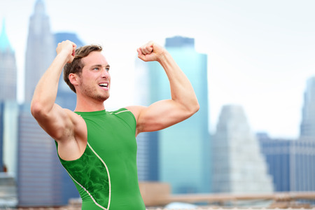 Winning cheering celebrating athlete fitness runner flexing muscles after running with Manhattan New York City skyline in background. photo