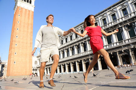 marco: Travel couple in love having playful fun in Venice holding hands running laughing in Venice, Italy on Piazza, San Marco. Happy young couple on travel vacation on St Marks Square. Happy woman and man.
