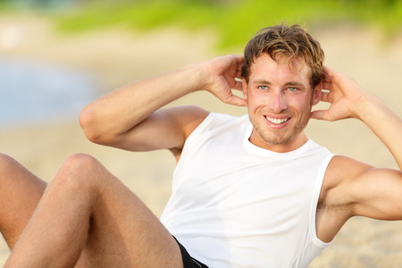 Fitness man doing crunches sit-ups on beach exercise outside. Fit male athlete exercising sit ups training on beautiful beach. Handsome sport model in cross training workout outdoors. photo
