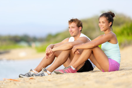 taking a break: Sporty runners resting sitting before run on beach. Running athletes couple man and woman taking a break after jogging. Fit sport fitness couple living healthy active lifestyle.