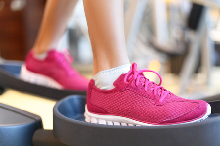 Fitness moonwalker treadmill equipmenti in gym. Closeup of women feet during exercise training on moonwalker. Exercising shoes. Stock Photo