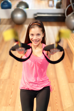 Fitness suspension training woman excising in gym. Asian woman doing strength exercise in fitness center. photo
