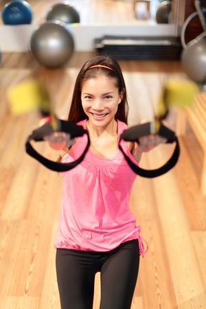 levantar pesas: Mujer capacitación suspensión de fitness en el gimnasio de la escisión. Mujer asiática que hace ejercicio de fuerza en el gimnasio.