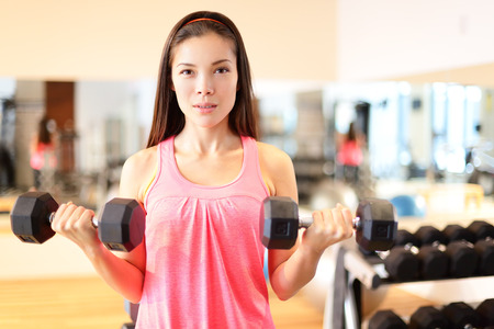 Gym woman strength training lifting dumbbell weights in biceps curl exercise. Female fitness girl exercising indoor in fitness center. Beautiful fit mixed race Asian Caucasian model training. photo