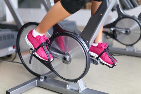 회전 바퀴 자전거 운동. 피트니스 센터에서 자전거를 절개하는 여자. 페달의 근접 촬영입니다. 전문 피트니스 센터 장비.