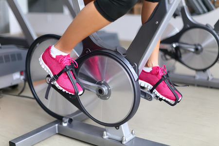 indoors: Exercise bike with spinning wheels. Woman excising biking in fitness center. closeup of pedals. Professional fitness center equipment. Stock Photo