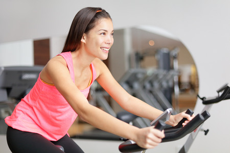 Exercise bike fitness woman excising with bike wheel spinning. Fit female model working out training indoor in fitness center.