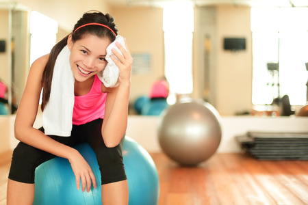 toalla: Mujer de la aptitud en el gimnasio descansando sobre pelota de pilates pelota  ejercicio sudoraci�n usando toalla que se relaja despu�s de un entrenamiento. Hermosa modelo de fitness multirracial en el gimnasio.
