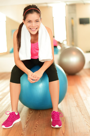 Fitness woman in gym resting on pilates ball  exercise ball relaxing after training. Beautiful multiracial fitness model in gym.