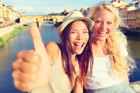 bff: Girlfriends in city happy giving thumbs up. Women girl friends on travel in Florence. Cheerful girlfriends thumbs up smiling happy portrait outdoor by Ponte Vecchio during vacation holidays in Florence, Tuscany, Italy, Europe. Stock Photo