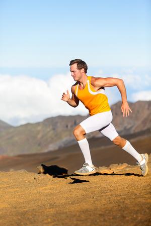sprinting: Runner. Running man on cross country trail run marathon in beautiful landscape nature.