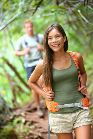 Hiking woman. Happy hiker girl with backpack trekking in forest smiling. photo