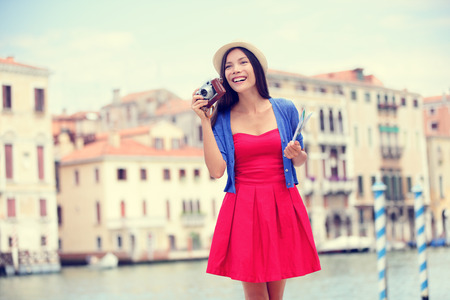 people travelling: Travel tourist woman with camera and map in Venice, Italy. Vintage retro style Asian girl on vacation smiling happy by Grand Canal. Mixed race Asian Caucasian girl having fun traveling outdoors.
