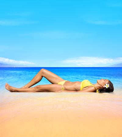 ビーチ旅行、高級スパ リトリート リゾート砂で横になっている太陽の下でリラックスした日光浴の女性。女性の日焼けを楽しむ太陽。幸せな笑みを