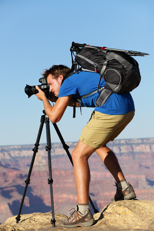 Photographer in Landscape nature in Grand Canyon taking picture photos with SLR camera and tripod during hike on south rim. Young man hiker enjoying landscape in Grand Canyon, Arizona, USA. photo