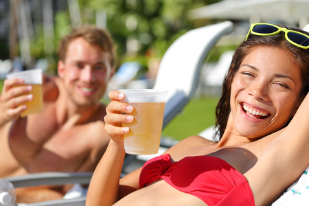 bikini couple: People drinking beer at relaxing at beach resort having fun enjoying spring break. Young couple relaxing drinking alcoholic drink on summer vacation holidays travel. Stock Photo