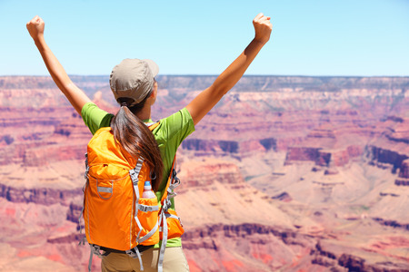 Success winner person happy hiker in Grand Canyon. Woman cheering with arms raised up in winning gesture enjoying the beautiful landscape. Hiking girl wearing backpack during summer in, Arizona, USA. Stock Photo