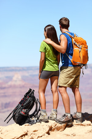 People hiking - Hikers in Grand Canyon. Hiking couple looking enjoying at view of nature landscape wearing backpacks. Young man and woman hiker relaxing after hike in Grand Canyon, Arizona, USA photo